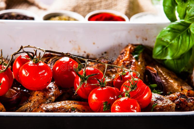 Grilled chicken wings with baked potatoes and vegetables. With sauce royalty free stock photo