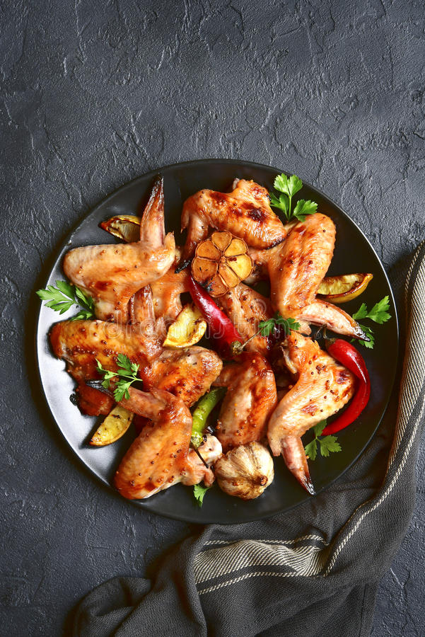 Grilled chicken wings on a black plate.Top view. royalty free stock image