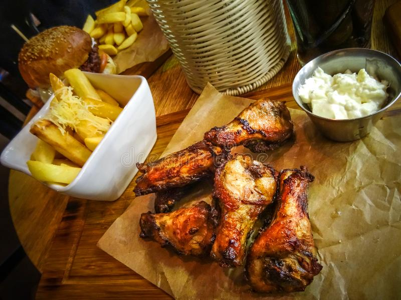 Grilled chicken wings and legs, garlic sauce, hamburger and potato chips royalty free stock images