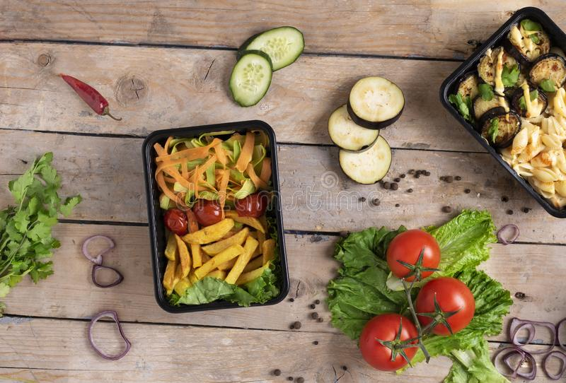 Two plastic containers with grilled chicken wings and raw vegetables on rustic background, vegetables salad  and micro greens stock images
