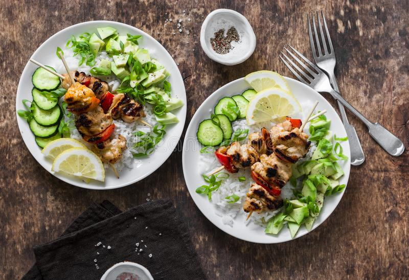 Grilled chili honey lime chicken skewers with rice and avocado salsa on wooden background, top view. stock photos