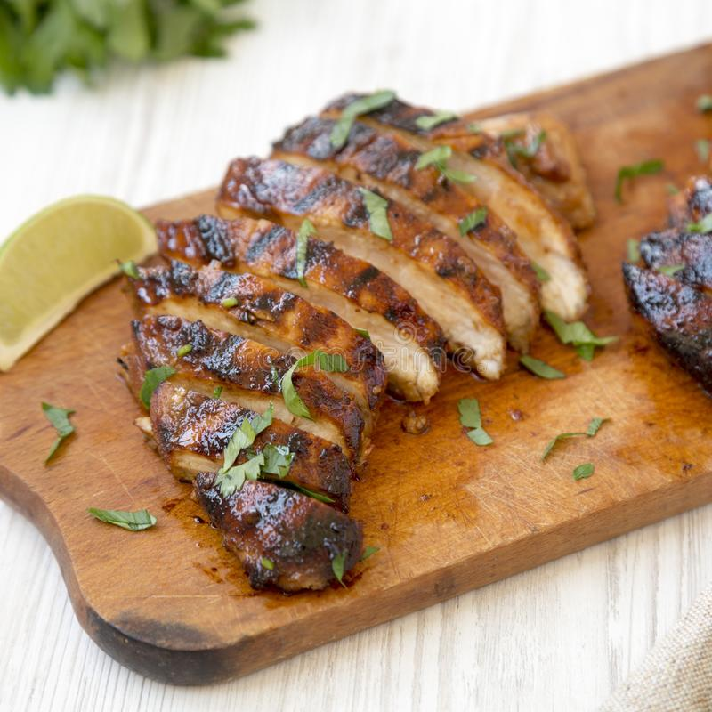 Grilled chipotle chicken breast on a rustic wooden board on a white wooden background, low angle view. Closeup.  royalty free stock images
