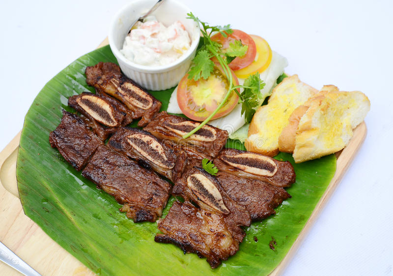 Grilled chopped pork ribs with bread and tomatoes on banana leaf stock photography
