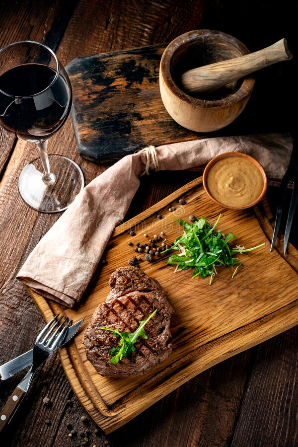 Free Grilled Chuck Beef Steak With Wine, Knife And Fork On A Wooden Board. Whole Roast Piece Of Meat Royalty Free Stock Photo - 185622565