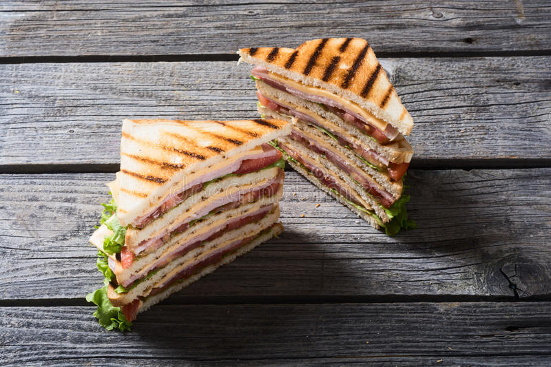 Grilled club sandwich. Club sandwich with bacon, tomato, cucumber and herbs stock image