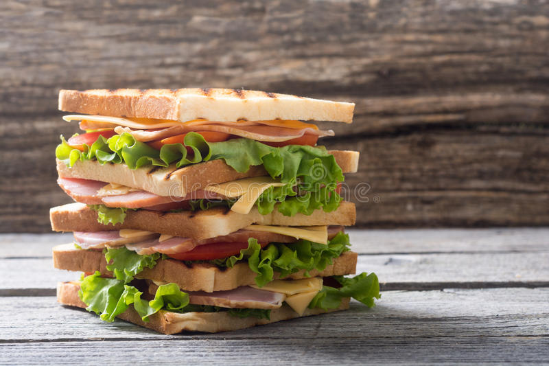 Grilled club sandwich. Club sandwich with bacon, tomato, cucumber and herbs stock photos