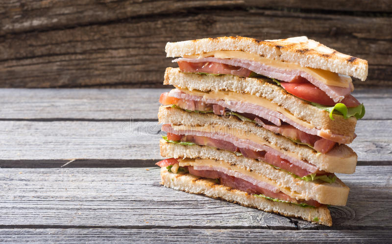 Grilled club sandwich. Club sandwich with bacon, tomato, cucumber and herbs stock photo
