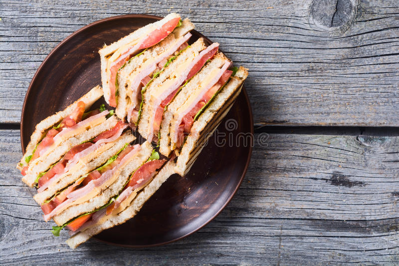 Grilled club sandwich. Club sandwich with bacon, tomato, cucumber and herbs . Top view stock photos