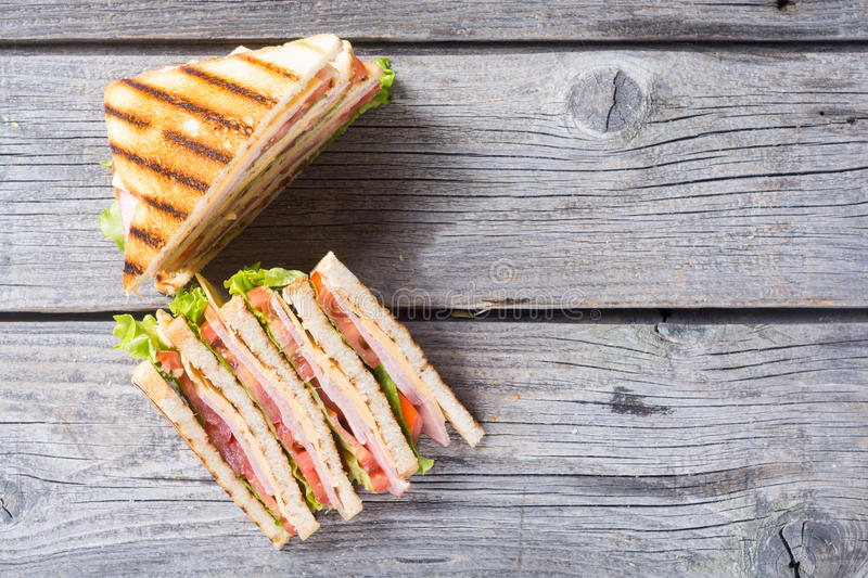 Grilled club sandwich. Club sandwich with bacon, tomato, cucumber and herbs . Top view with space for text stock images