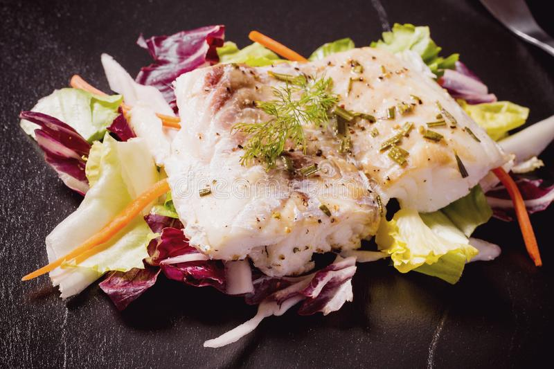 Grilled cod fillet with salad on black slate plate stock photo