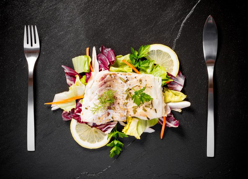 Grilled cod fillet with salad on black slate plate. Top view royalty free stock photography