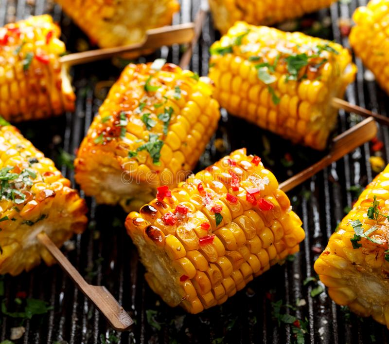 Grilled corn on the cob with butter, herbs, salt and aromatic spices on the grill plate stock image