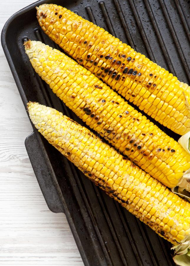 Grilled corn on the cob in a grilling pan, top view. Overhead, from above, flat lay.  stock photo