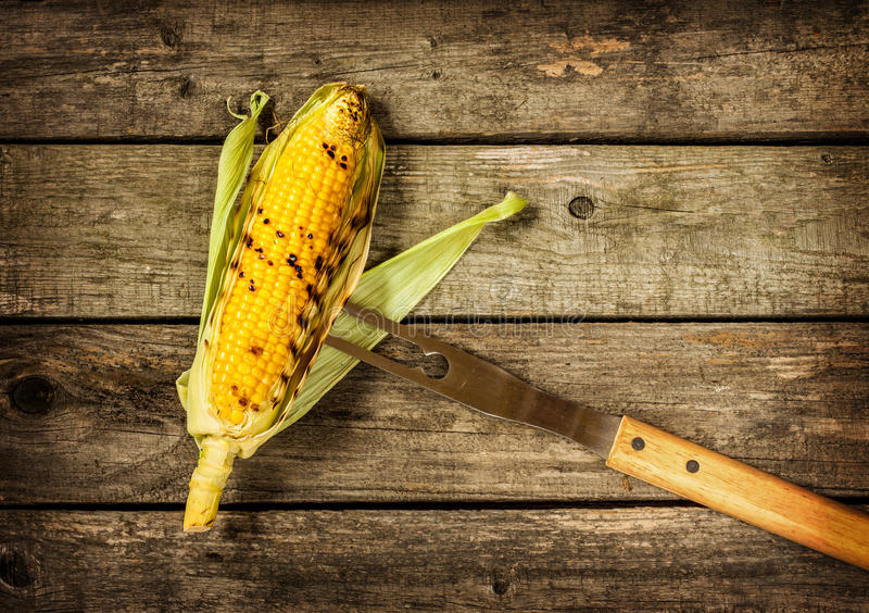 Grilled corn cob on vintage wood background royalty free stock photo