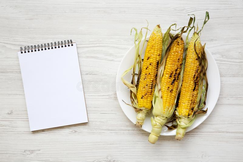 Grilled corn cobs on a round plate and blank notepad over white wooden table, top view. royalty free stock photos