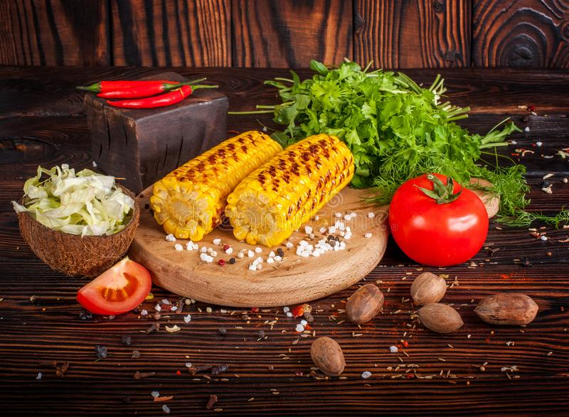 Grilled corn with spices, herbs and tomatoes stock image