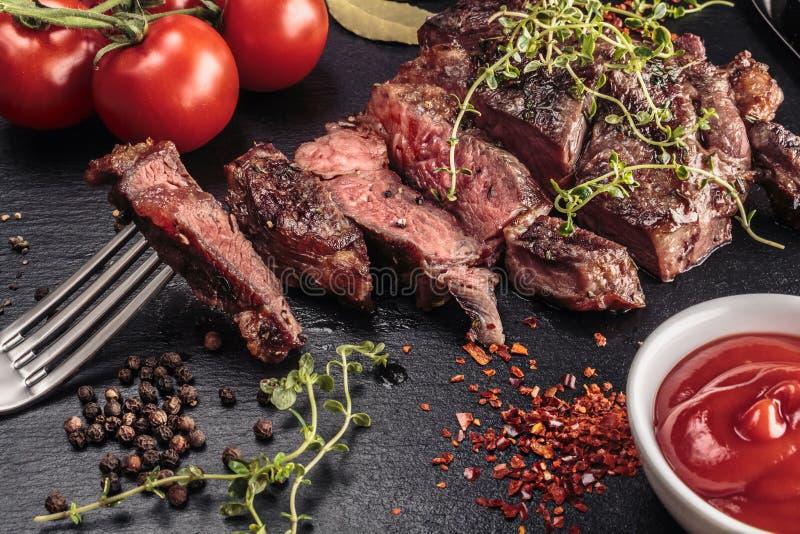Grilled cortou o bife na placa da ardósia com ervas imagens de stock royalty free