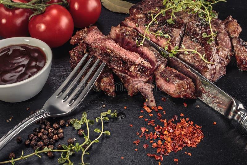 Grilled cortou o bife na placa da ardósia com ervas foto de stock royalty free