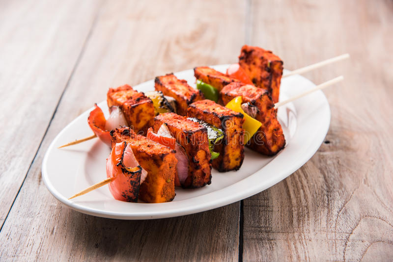 Grilled cottage cheese or also known as Paneer Tikka Kebab or chili paneer or chilli paneer or tandoori paneer in india India, bar. Becued in red sauce stock image