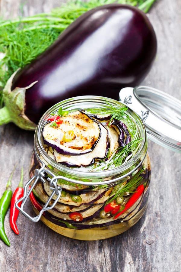 Grilled a coupé en tranches l'aubergine avec le piment dans le pot en verre sur la table rustique images libres de droits