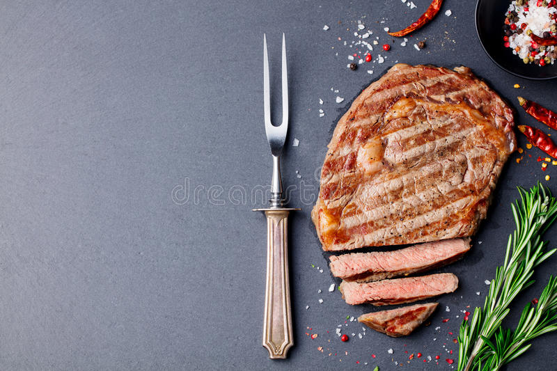 Grilled a coupé en tranches le bifteck de boeuf sur la table de pierre d'ardoise Vue supérieure Copiez l'espace photos libres de droits