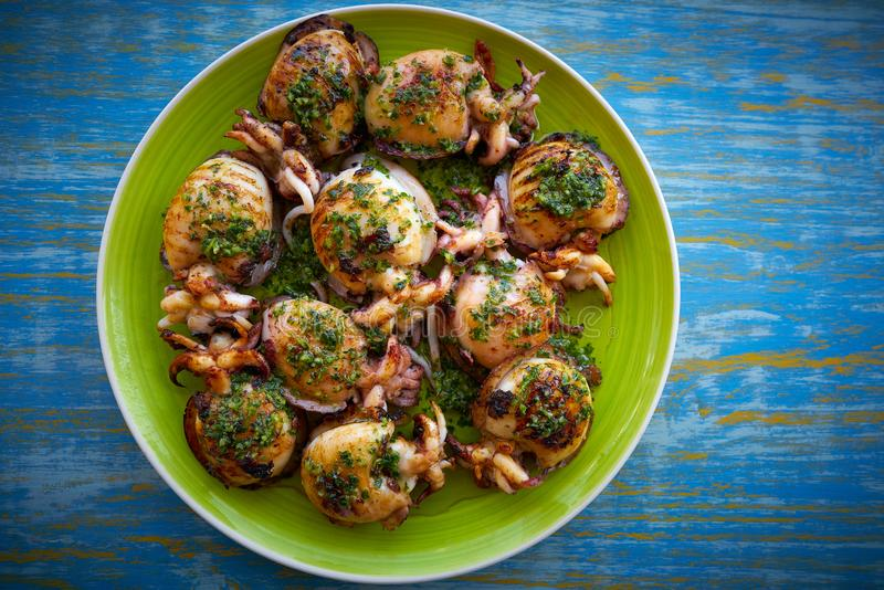 Grilled cuttlefish squid with parsley sauce royalty free stock images
