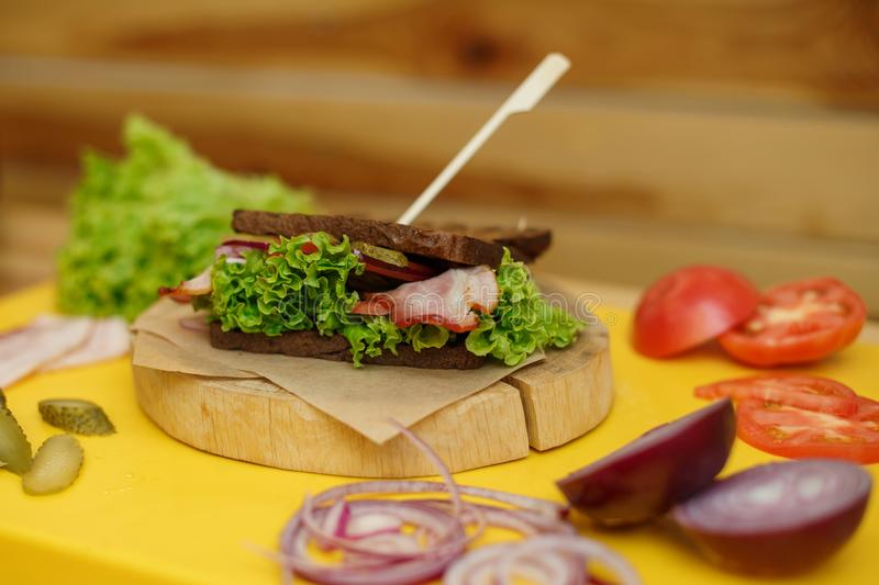 Grilled dark bread sandwich on wooden plate on yellow board.  stock images