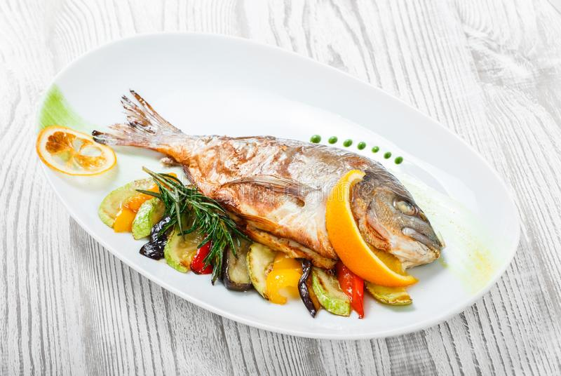 Grilled dorado fish with baked vegetables and rosemary on plate on wooden background close up. royalty free stock images