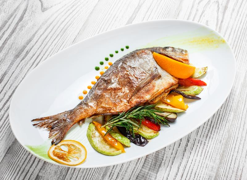 Grilled dorado fish with baked vegetables and rosemary on plate on wooden background close up. stock photo