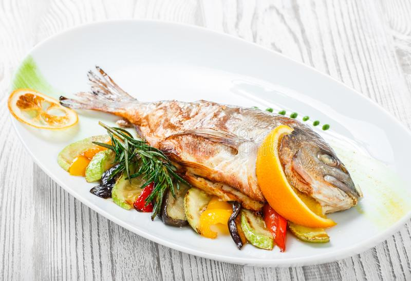 Grilled dorado fish with baked vegetables and rosemary on plate on wooden background close up. royalty free stock image
