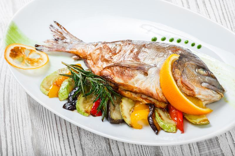 Grilled dorado fish with baked vegetables and rosemary on plate on wooden background close up. stock photography