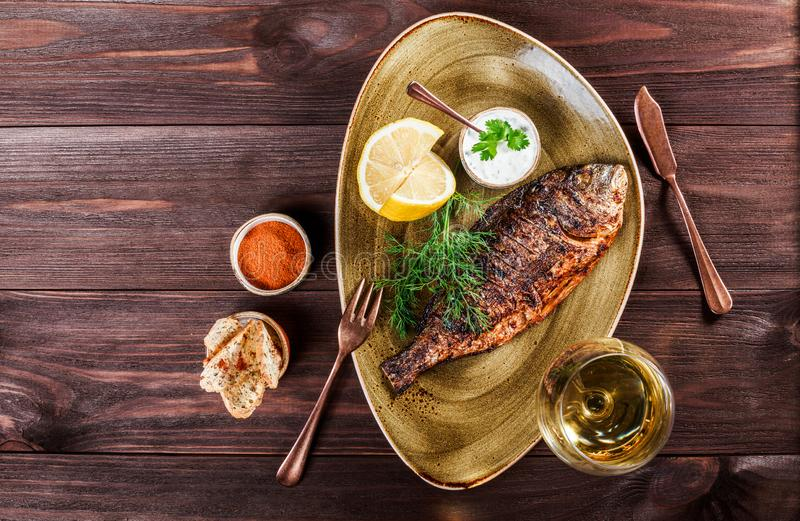 Grilled dorado fish with lemon and greens on plate on wooden background. Delicious dish of seafood. stock photo