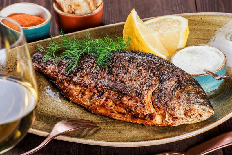 Grilled dorado fish with lemon and greens on plate on wooden background. Delicious dish of seafood.  royalty free stock images