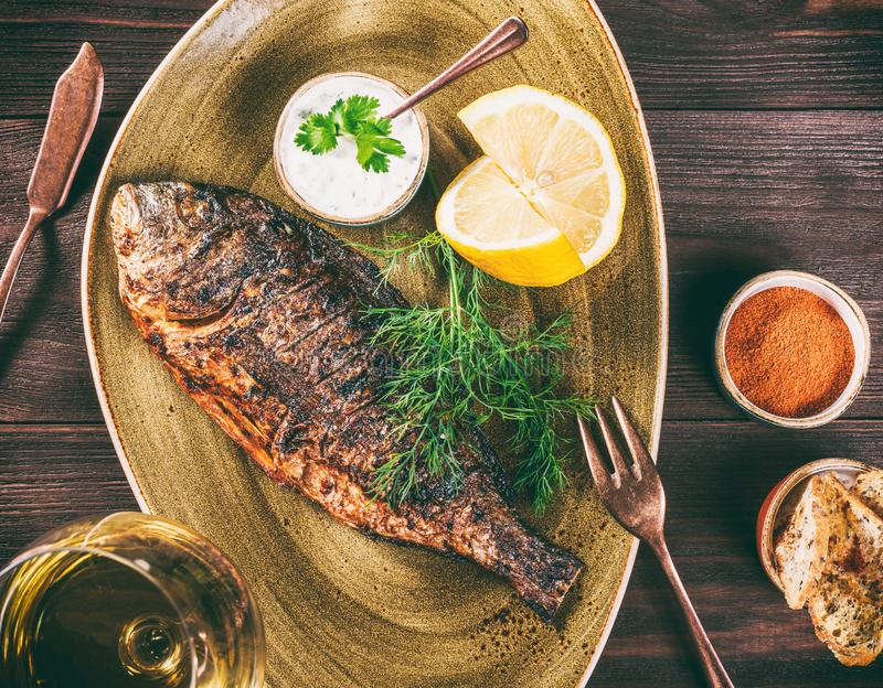 Grilled dorado fish with lemon and greens on plate on wooden background. royalty free stock image