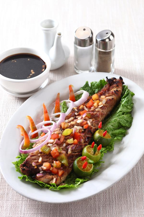 Grilled dtuna belly. On white plate with dipping sauce royalty free stock image