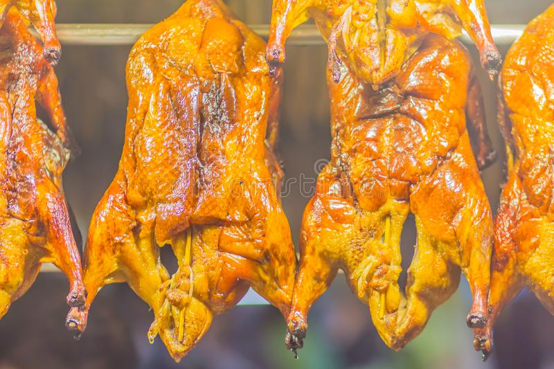 Grilled ducks for sale at the street food market. Full body grilled ducks in the showcase at the Chinese food shop. stock photo