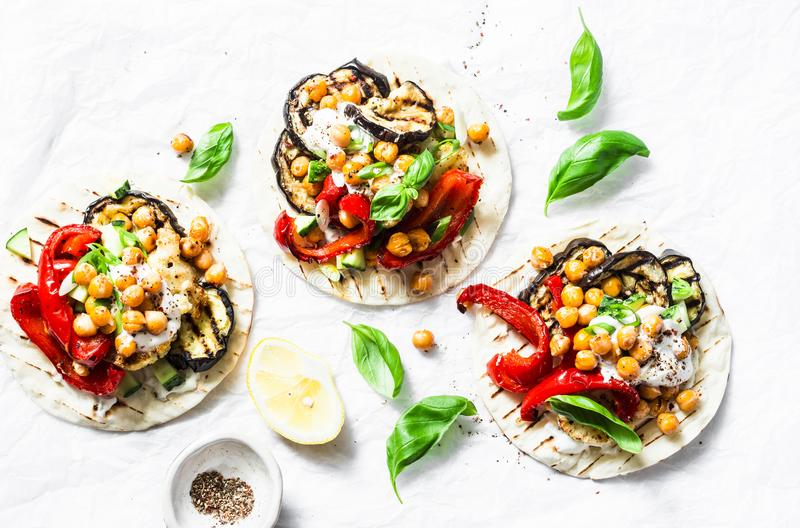Grilled eggplant, sweet peppers, cauliflower and spicy chickpeas vegetarian tortillas on a light background, top view. Healthy foo royalty free stock images
