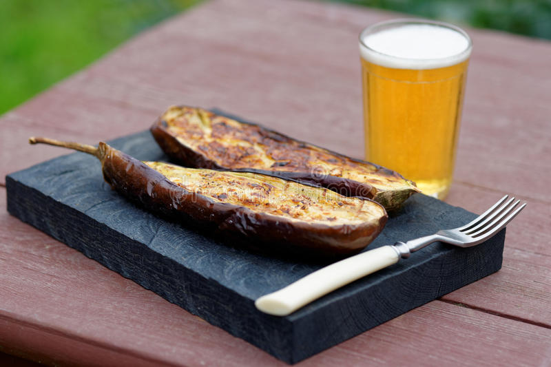 Grilled eggplant on table. Grilled eggplant and a glass of beer on table stock photos