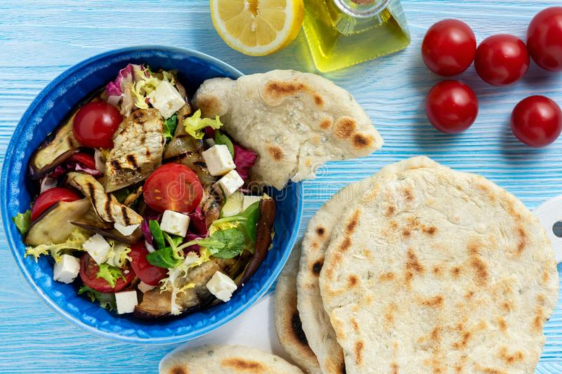 Grilled eggplant, tomatoes and feta cheese salad with flatbread, mediterranean cuisine. Grilled eggplant, tomatoes and feta cheese salad with flatbread royalty free stock images
