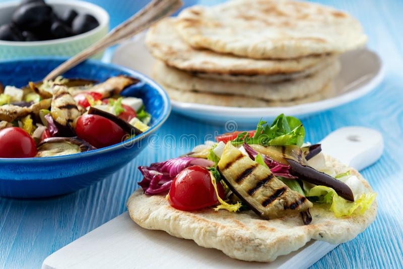 Grilled eggplant, tomatoes and feta cheese salad with flatbread, mediterranean cuisine. Grilled eggplant, tomatoes and feta cheese salad with flatbread stock photography