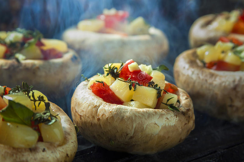 Grilled and filled mushroom. Cheese and vegetables filled champignons stock photos