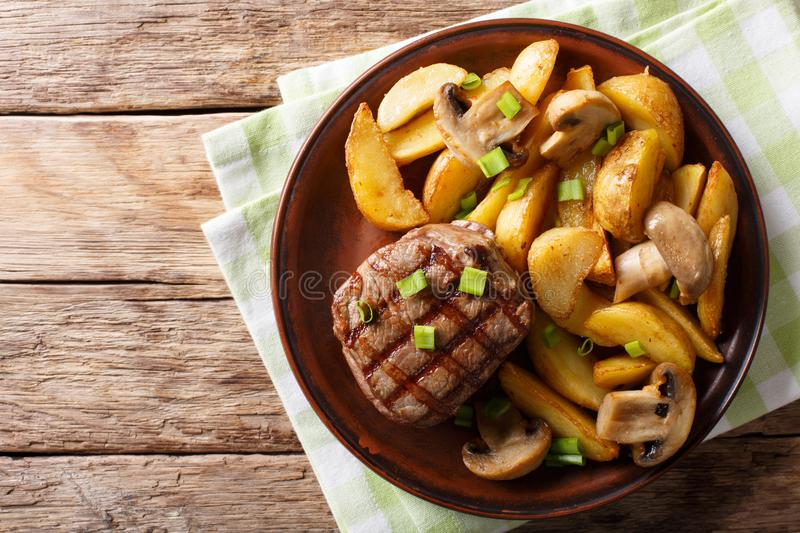 Grilled fillet mignon with potatoes and mushrooms close-up. Horizontal top view stock image
