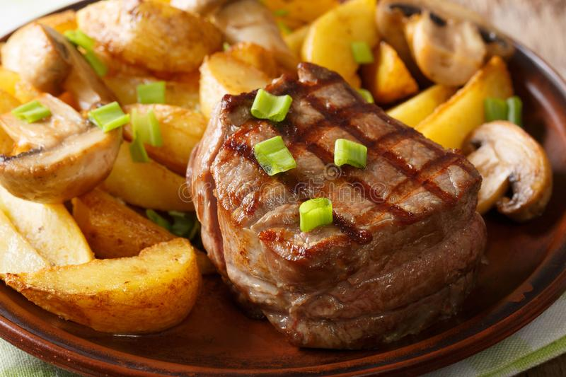 Grilled fillet mignon with potatoes and mushrooms close-up. horizontal stock image