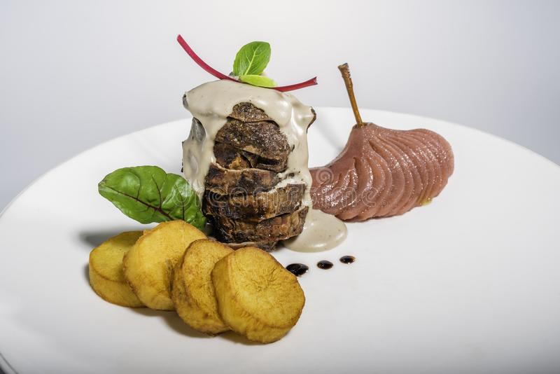 Grilled fillet mignon. With potatoes and pear boiled in wine stock photography