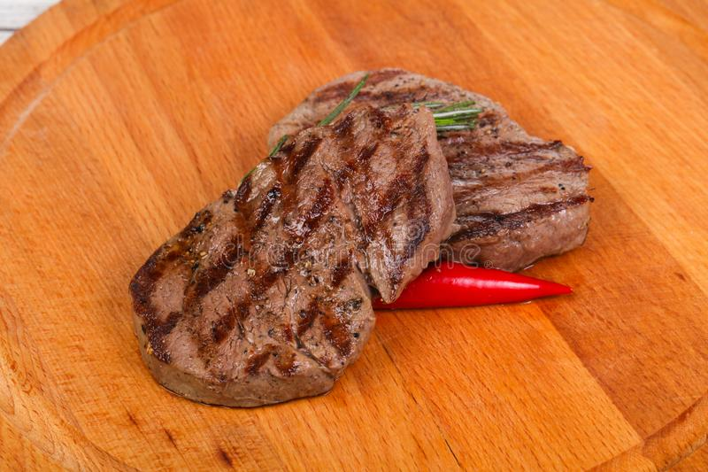 Grilled Fillet Mignon with rosemary and chili pepper. Over the wooden background stock images