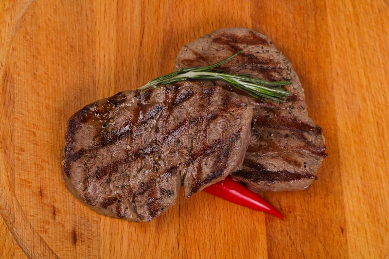 Grilled Fillet Mignon with rosemary and chili pepper. Over the wooden background stock photography