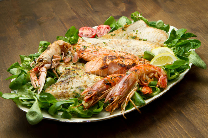 Grilled fish with chips and vegetables royalty free stock photography