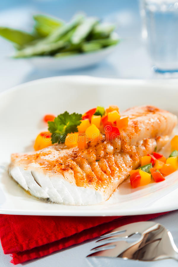 Grilled fish with colorful sweet peppers stock image