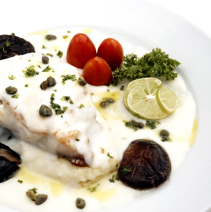Grilled fish with cream sauce. On plate stock photo