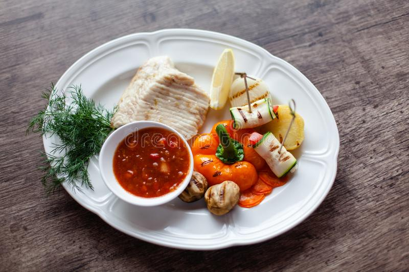 Grilled fish fillet served with vegetables and sauce stock image
